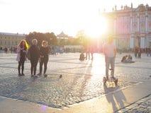 Το άτομο σε Gyroscooter Άνθρωποι στους γύρους Gyroscooter στο ηλιοβασίλεμα στο τετράγωνο παλατιών, μεταξύ των τουριστών στην Άγιο Στοκ εικόνες με δικαίωμα ελεύθερης χρήσης