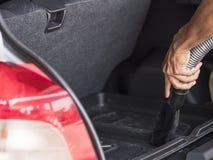 Το άτομο σκουπίζει το αυτοκίνητο με ηλεκτρική σκούπα Στοκ φωτογραφία με δικαίωμα ελεύθερης χρήσης