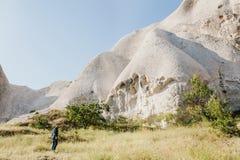 Το άτομο στέκεται δίπλα στους όμορφους βράχους και θαυμάζει το τοπίο σε Cappadocia στην Τουρκία Το τοπίο Cappadocia Στοκ Φωτογραφία