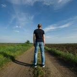 Το άτομο στέκεται με την πλάτη του στον τομέα και κοιτάζει επίμονα Στοκ Φωτογραφία