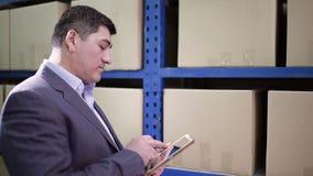 Το άτομο στέκεται στην αποθήκη εμπορευμάτων και κρατά την ταμπλέτα απόθεμα βίντεο