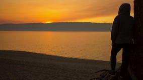 Το άτομο στέκεται στην παραλία και συλλογίζεται ένα όμορφο ηλιοβασίλεμα Χρονικό σφάλμα 4K απόθεμα βίντεο