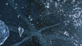 Το άτομο στα γάντια συνθλίβει τον πάγο στον πάγο κίνηση αργή Οι κινήσεις καμερών πίσω από τον πάγο Ένα κομμάτι του πάγου είναι πο φιλμ μικρού μήκους