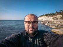 Το άτομο στα γυαλιά παίρνει selfie εν πλω την παραλία και λικνίζει το υπόβαθρο, έννοια ταξιδιού στοκ φωτογραφίες