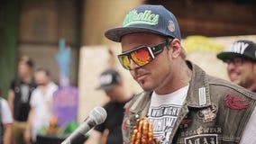 Το άτομο στα γυαλιά ηλίου, ΚΑΠ μιλά στο μικρόφωνο Χρυσός αριθμός των χεριών επίκλησης lottery 100f 2 θερινό velvia ταινιών fujich απόθεμα βίντεο