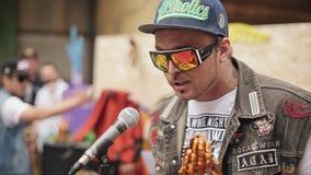 Το άτομο στα γυαλιά ηλίου μιλά στο μικρόφωνο Χρυσός αριθμός των χεριών επίκλησης lottery 100f 2 θερινό velvia ταινιών fujichrome  απόθεμα βίντεο