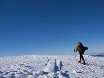 Το άτομο στα πλέγματα σχήματος ρακέτας στα βουνά Στοκ εικόνα με δικαίωμα ελεύθερης χρήσης
