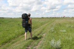 Το άτομο στα σορτς με ένα σακίδιο πλάτης που πηγαίνει στον αγροτικό δρόμο στοκ φωτογραφία με δικαίωμα ελεύθερης χρήσης