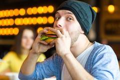 Το άτομο στα χέρια κρατά burger Άτομο που τρώει burger στον καφέ Στοκ Εικόνα