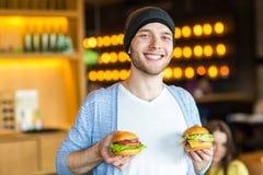 Το άτομο στα χέρια κρατά burger Άτομο που τρώει burger στον καφέ Στοκ Εικόνες