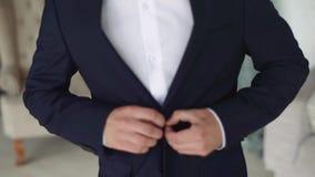 Το άτομο στερεώνει το κουμπί στο σακάκι του Επιχειρηματίας στο μπλε επιχειρησιακό κοστούμι απόθεμα βίντεο