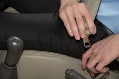 Το άτομο στερεώνει τη ζώνη ασφαλείας στο αυτοκίνητο πρίν οδηγεί αυτοκινητικές δημόσιες σχέσεις ασφάλειας Στοκ Εικόνα
