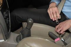 Το άτομο στερεώνει τη ζώνη ασφαλείας στο αυτοκίνητο πρίν οδηγεί αυτοκινητικές δημόσιες σχέσεις ασφάλειας Στοκ εικόνες με δικαίωμα ελεύθερης χρήσης