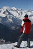 Το άτομο στην άκρη του απότομου βράχου στα χιονώδη βουνά Στοκ φωτογραφία με δικαίωμα ελεύθερης χρήσης
