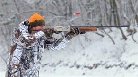 Το άτομο στην κάλυψη χρεώνει ένα κυνηγετικό όπλο με τις κασέτες, τους στόχους και τους βλαστούς με ένα κυνηγετικό όπλο 50 fps απόθεμα βίντεο