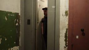 Το άτομο στην ΚΑΠ με τον περίπατο σακιδίων πλάτης στενεύει έξω τον ανελκυστήρα σπίτι παλαιό Ragged τοίχοι απόθεμα βίντεο