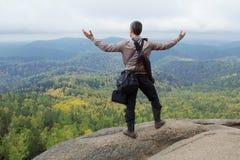 Το άτομο στην κορυφή του βουνού απολαμβάνει την ομορφιά της φύσης Για να επιτύχουν τους στόχους στοκ εικόνα