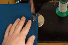 Το άτομο στην παλαιά ράβοντας μηχανή είναι ραμμένο μπλε ύφασμα στο εγχώριο εργαστήριο Στοκ Εικόνες