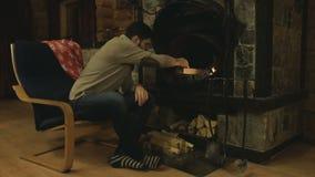 Το άτομο στην πολυθρόνα από την εστία στα θερμά κρύα χέρια Μια θερμή άνετη πυρκαγιά, μια καίγοντας πυρκαγιά στην εστία άνετος φιλμ μικρού μήκους