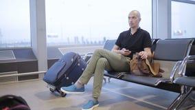 Το άτομο στη αίθουσα αναμονής στον αερολιμένα που αναμένει την πτήση, χρησιμοποιεί ένα smartphone και τις δεσποινίδες απόθεμα βίντεο