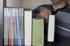 Το άτομο στη βιβλιοθήκη παίρνει ένα βιβλίο μακριά - - ράφι Στοκ εικόνα με δικαίωμα ελεύθερης χρήσης