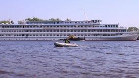 Το άτομο στη διογκώσιμη βάρκα κινείται κοντά στο μεγάλο σκάφος απόθεμα βίντεο