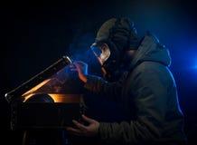Το άτομο στη μάσκα αερίου ανοίγει μια παλαιά βαλίτσα Στοκ εικόνα με δικαίωμα ελεύθερης χρήσης