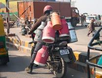 Το άτομο στη μοτοσικλέτα με τα δοχεία πίσω από την πλάτη στο δρόμο στις 28 Ιανουαρίου 2014 σε Agra, Ινδία στοκ φωτογραφίες