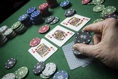 Το άτομο στοιχημάτισε τις κάρτες τους με τις ετικέττες για να κερδίσει το παιχνίδι πόκερ στοκ εικόνα