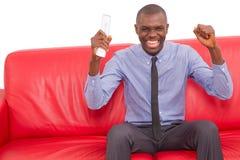 Το άτομο στον καναπέ με τον τηλεχειρισμό χαίρεται στοκ φωτογραφία με δικαίωμα ελεύθερης χρήσης