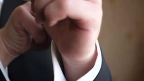 Το άτομο στον μπλε δεσμό και το μαύρο σακάκι ισιώνει το μανίκι ενός άσπρου πουκάμισου Κινηματογράφηση σε πρώτο πλάνο απόθεμα βίντεο