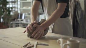 Το άτομο στον ξύλινο πίνακα στο εργαστήριο ζυμώνει τη μάζα αργίλου για την κεραμική απόθεμα βίντεο