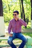 Το άτομο στον πάγκο, με τον καφέ ή το τσάι, που μιλά στο τηλέφωνο, το καλοκαίρι στα γυαλιά και ένα πουκάμισο στα ξύλα Στοκ φωτογραφία με δικαίωμα ελεύθερης χρήσης