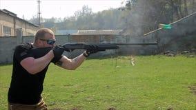 Το άτομο στους στόχους και τους βλαστούς γυαλιών με ένα κυνηγετικό όπλο 50 fps απόθεμα βίντεο