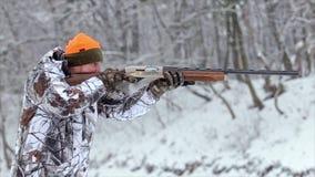Το άτομο στους στόχους και τους βλαστούς κάλυψης με ένα κυνηγετικό όπλο 50 fps απόθεμα βίντεο