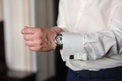 Το άτομο στο άσπρο πουκάμισο φορά τα ρολόγια Στοκ εικόνα με δικαίωμα ελεύθερης χρήσης