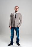 Το άτομο στο γκρίζο σακάκι και το τζιν παντελόνι που κρατά την παραδίδουν γεια Στοκ Φωτογραφίες