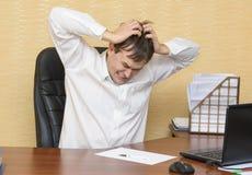 Το άτομο στο γραφείο αρπάζει θυμωμένα το κεφάλι του Στοκ φωτογραφία με δικαίωμα ελεύθερης χρήσης