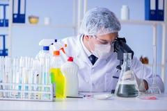 Το άτομο στο εργαστήριο που εξετάζει το νέο καθαρίζοντας απορρυπαντικό λύσης Στοκ Φωτογραφία