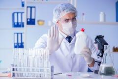 Το άτομο στο εργαστήριο που εξετάζει το νέο καθαρίζοντας απορρυπαντικό λύσης Στοκ Εικόνες
