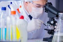 Το άτομο στο εργαστήριο που εξετάζει το νέο καθαρίζοντας απορρυπαντικό λύσης Στοκ εικόνα με δικαίωμα ελεύθερης χρήσης