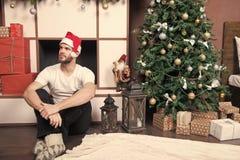 Το άτομο στο καπέλο santa κάθεται στην εστία στοκ εικόνες με δικαίωμα ελεύθερης χρήσης