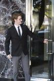Το άτομο στο κοστούμι ανοίγει μια πόρτα στοκ εικόνα με δικαίωμα ελεύθερης χρήσης