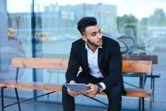 Το άτομο στο κοστούμι Αραβικά βάζει στα γυαλιά ηλίου με την ταμπλέτα κοντά στην επιχείρηση Στοκ Φωτογραφίες