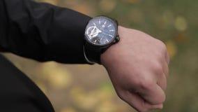 Το άτομο στο κοστούμι εξετάζει το ρολόι έξω απόθεμα βίντεο