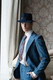 Το άτομο στο κοστούμι και το καπέλο που στέκεται στο παράθυρο που βάζει δικοί του παραδίδουν την τσέπη του Στοκ φωτογραφία με δικαίωμα ελεύθερης χρήσης