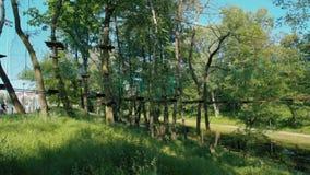 Το άτομο στο κράνος γλιστρά κάτω από τη γραμμή φερμουάρ στο υψηλό πάρκο σχοινιών περιπέτειας το καλοκαίρι απόθεμα βίντεο