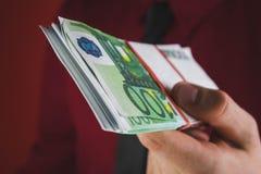 το άτομο στο κόκκινο κοστούμι άντεξε ένα wad των χρημάτων στο χέρι του στο κόκκινο υπόβαθρο στοκ εικόνες