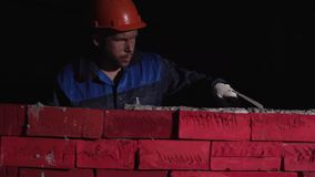 Το άτομο στο λειτουργώντας εξοπλισμό χτίζει έναν τοίχο του τούβλου απόθεμα Έννοια self-development Για να χτίσει μια σταδιοδρομία απόθεμα βίντεο
