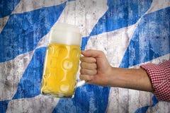 Το άτομο στο παραδοσιακό βαυαρικό πουκάμισο κρατά την κούπα της μπύρας Στοκ Εικόνα